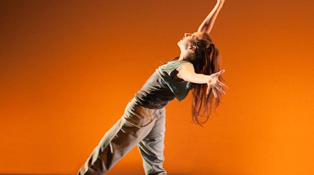 Woman dancing in front of orange background